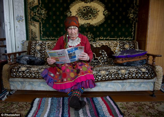 Resting her feet: Galina Koneva, reads a newspaper as she relaxes between rehearsals. 'They haven't seen much in this life except work,' said choir leader Olga Tuktareva