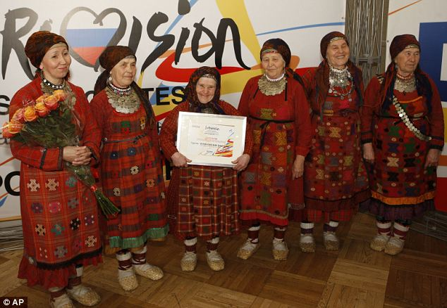 Proud: The Buranovo Grannies pose with their Eurovision certificate after winning the Russian nomination. It now hangs proudly in their village hall