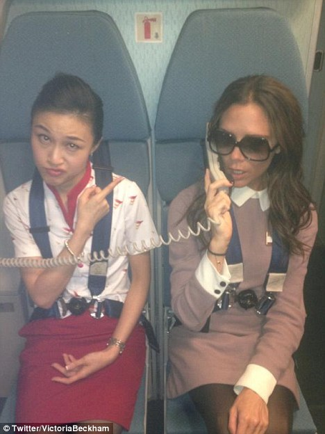 Doors to manual: Victoria Beckham tries her hand at being a flight attendant during a flight to Beijing