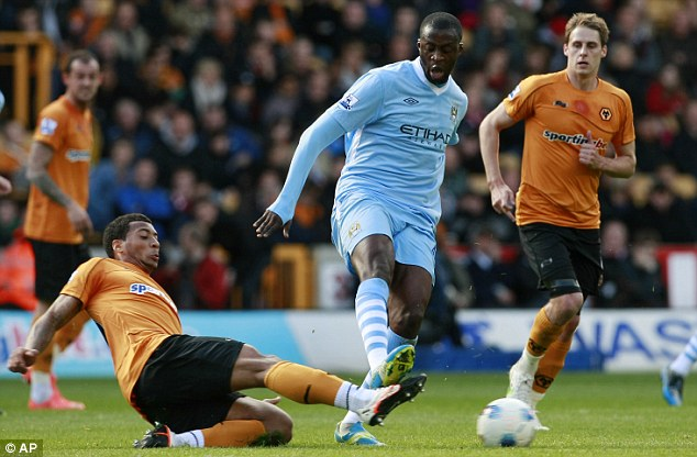 Struds up: Yaya Toure (centre) is challenged by Wolves' David Davis (left)