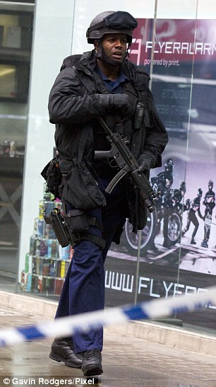 An armed officer stands by the cordon on Tottenham Court Road, as more equipment is thrown onto the street