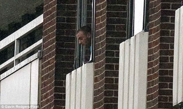 A man looks out of the window from which debris including a filing cabinet were thrown