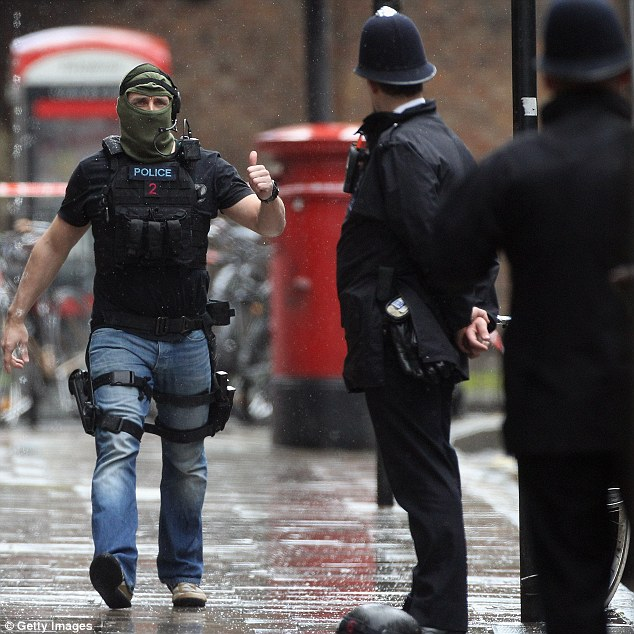 Job done: Armed police officers on the scene where the man threaten to blow himself up