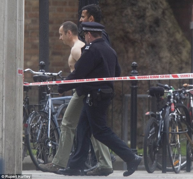 Led away: Police take the shirtless man away to a police van as the Tottenham Court Road siege comes to an end