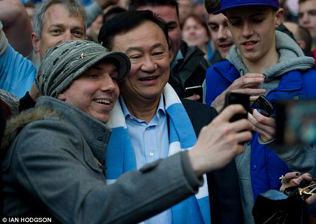 Familiar face: Former Manchester City chairman Thaksin Shinawatra poses with the home fans while one fan's sign summed it up for everyone (below)