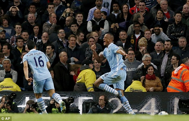 Heads up: The City captain leaps above Smalling to give the hosts the lead and wheels away to celebrate (below)