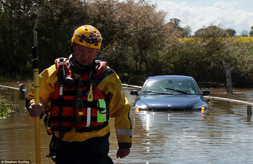 Salvage operation: A rescue worker returns after helping a man who became trapped in his BMW 5 Series after driving into three-foot-deep floodwater in Ingatestone, Essex