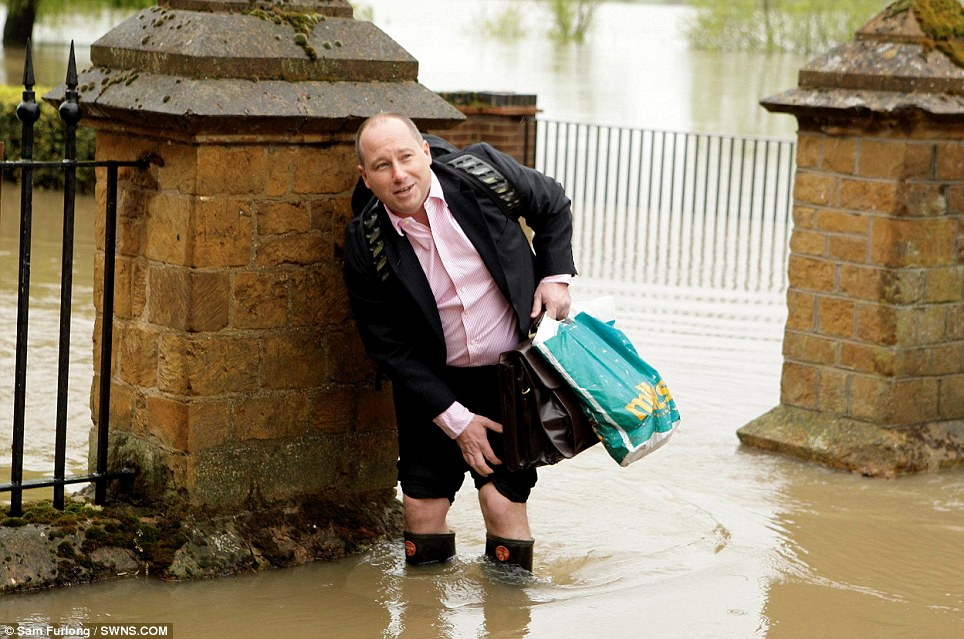 Welly, welly wet: A resident in Tewkesbury struggles to work this morning through foot-high floodwater, which has completely surrounded his home after the Severn and Avon rivers burst their banks from the heavy rainfall
