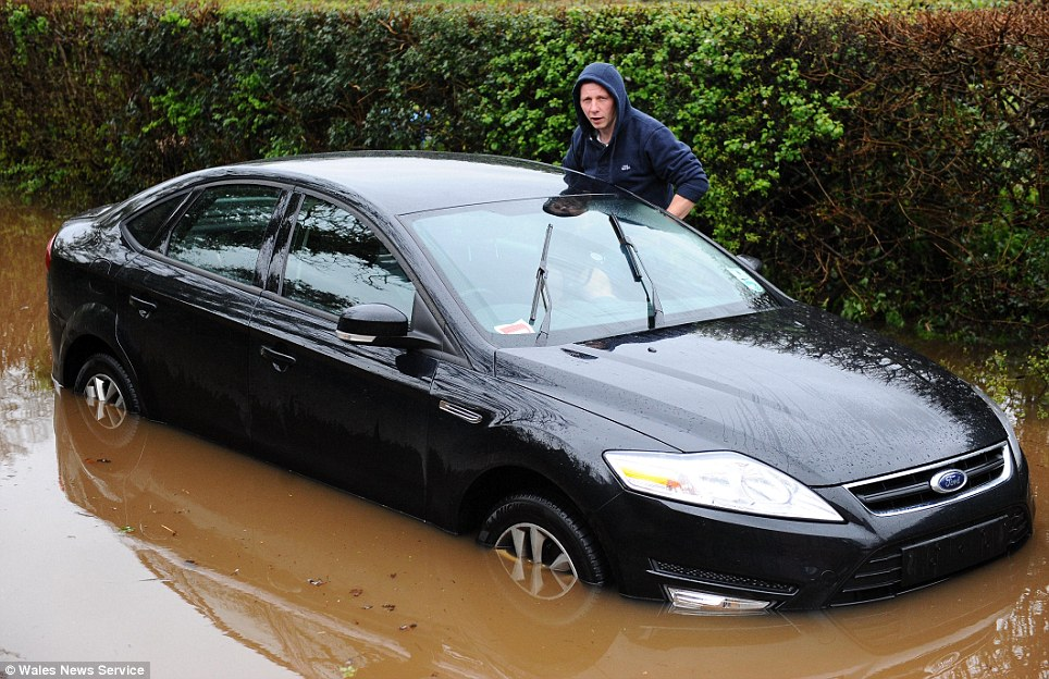 I think the engine's flooded: A motorist is caught in a flood near the village of Pendoylan near Cardiff in South Wales