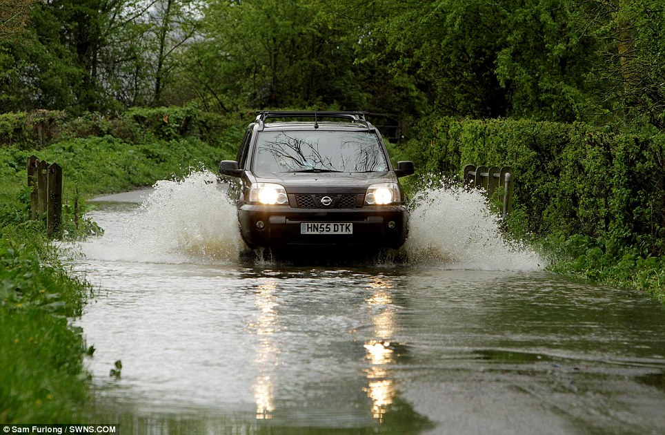 The flooding has made this country lane near Tewkesbury impassable to all but the sturdiest vehicles