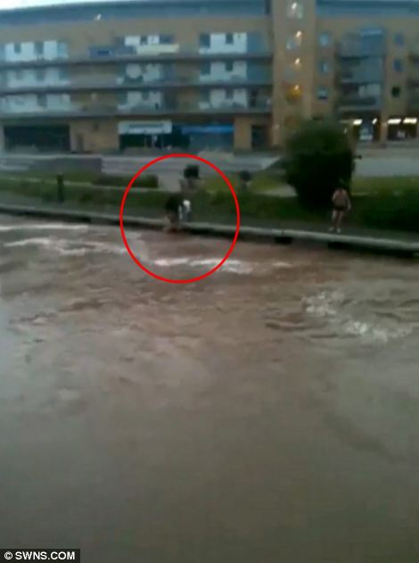 Help: The youth can be seen having reached the river bank after his dangerous dip and being helped from the water