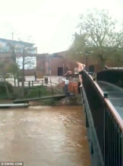 Brink: Youths can be seen on the bridge in their underwear, with one about to jump into the rain-swollen river in Taunton, Somerset