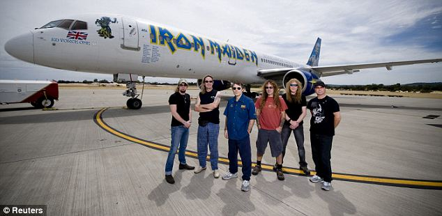 High flyer: Iron Maiden frontman Bruce Dickinson (blue shirt) has flown large passenger jets during his time away from prowling concert stages