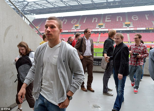 On the move: Podolski leaves a press conference in Cologne after talking about his Arsenal switch