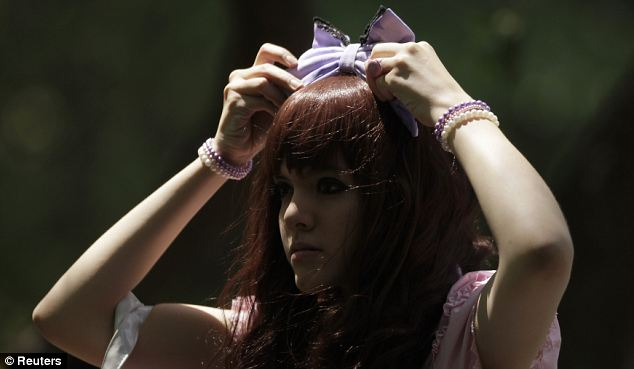 A member of the Lolitas Paradise club adjusts her headband