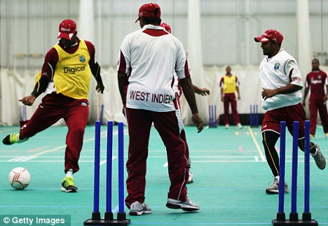 Having a ball: The Windies squad have a kickaround while the rain pours down outside