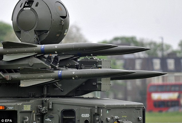In the line of fire: A London bus drives past surface to air missiles at an army cadet base in Blackheath, southeast London