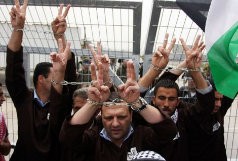 Rallying point: Protesters wearing symbolic chains gather outside a jail near the West Bank city of Ramallah last week in support of the hunger-strikers