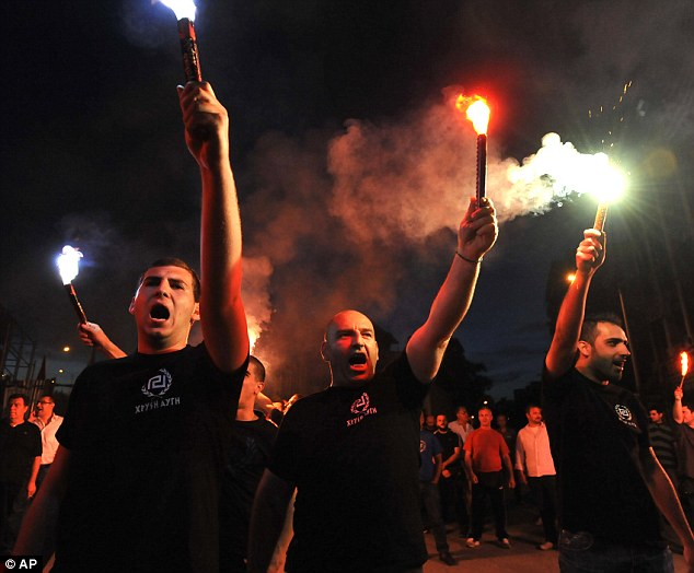 Rise of the far right: Dressed in black shirts and brandishing flares, these Golden Dawn supporters celebrate after they secured almost seven per cent of the vote
