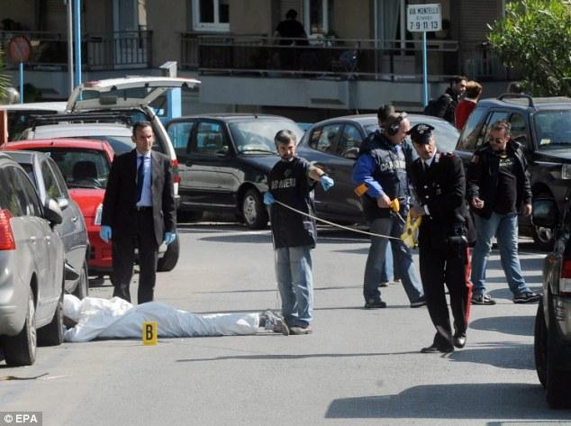 Cordoned off: Two men wearing helmets on a black Yamaha motorbike fired shots at Adinolfi