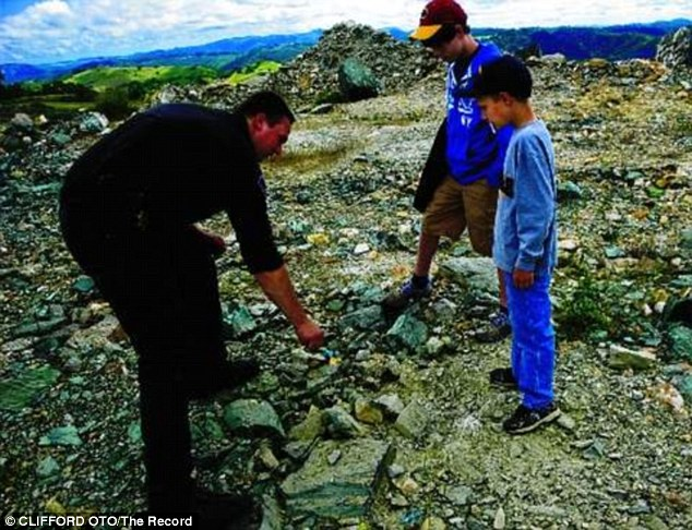 Rocks: A member of the bomb squad talks to Evan, 8, and his cousin Brandon, 14, about the rocks at Angels Camp