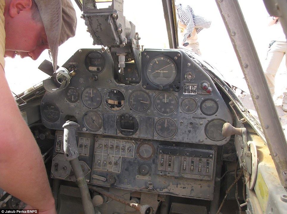 At the controls: The plane's cockpit, but there are fears over what will be left of it after locals began stripping parts and instruments for souvenirs and scrap