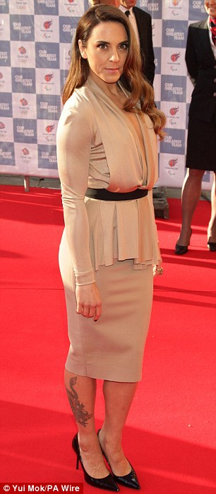 Showing off her legs: Melanie Chisholm wore a cream coloured knee-length dress and simple black heels