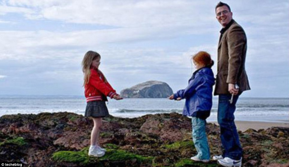 Proud papa: This dad watches on as his kids pluck an island out of the sea