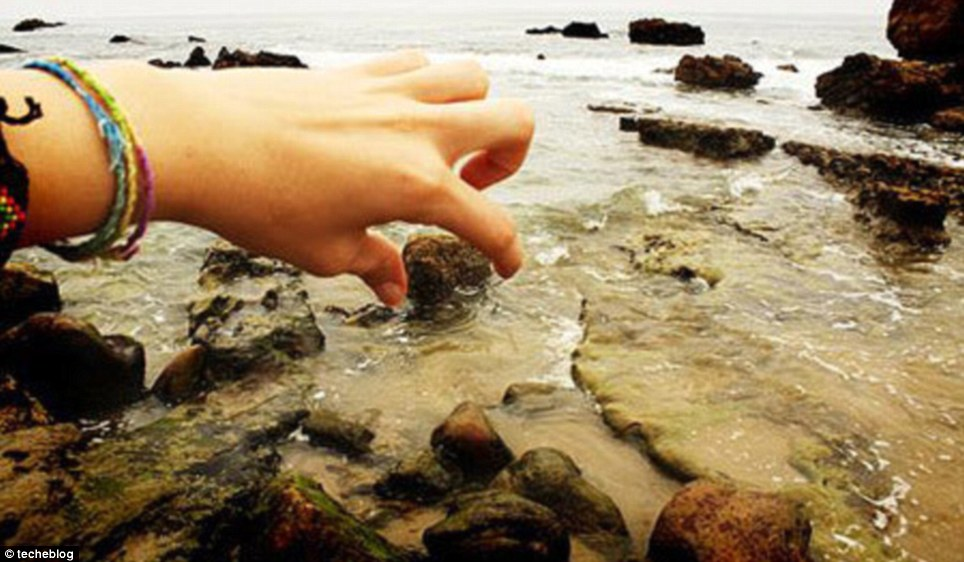 Rock'n'roll: A huge hand pulls boulders out of the sea