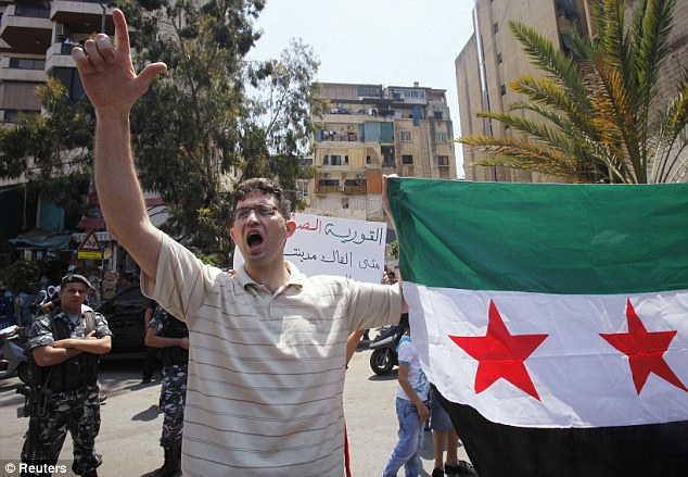 Uproar: A protester waves a Syrian opposition flag while shouting slogans, as Lebanese policemen stand guard, during a protest against Syria's President Bashar al-Assad yesterday