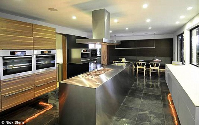 Whip up a meal: The Bulthaup kitchen has stunning Monobloc stainless steel island, floating appliance cubes, warm bronze and striped walnut cabinetry