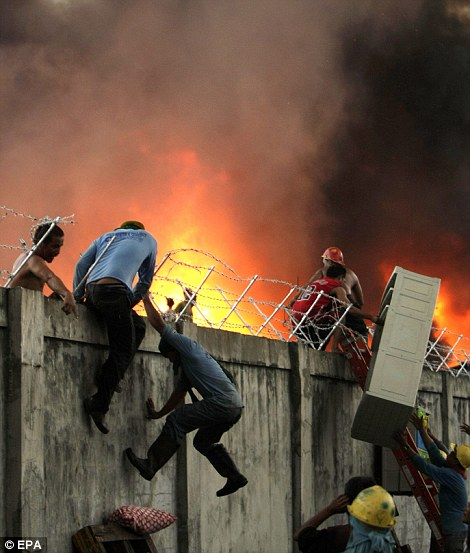 Escape: Shanty town residents navigate a barbed wire fence to escape from the blaze, left, while others run for their lives through the cluster of huts, right