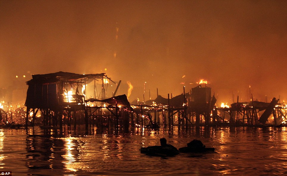 During the fire: A man watches helplessly from the water as the flames engulf the houses during the fire on Friday night