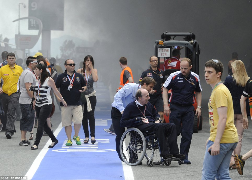 Concern: Sir Frank Williams is taken to safer surroundings following the pit-lane fire