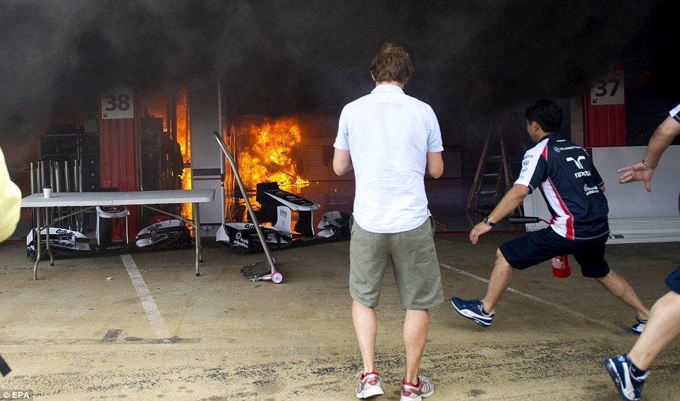 Shock: Workers look on in horror as the blaze starts to engulf the Williams garage