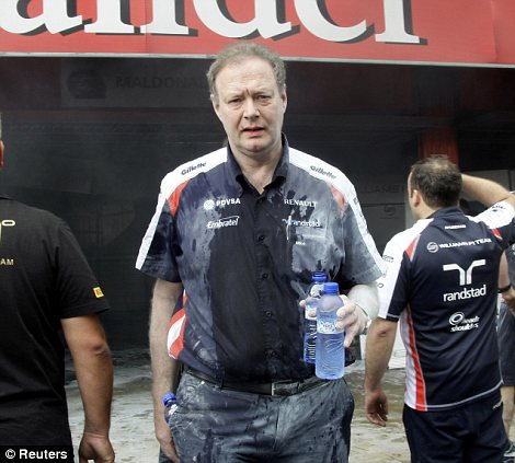 A Williams Formula One team crew member walks out of their garage