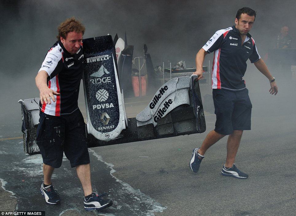 Salvaged: Racing team crews carry the front end of a car after a fire in the Williams racing pit stand