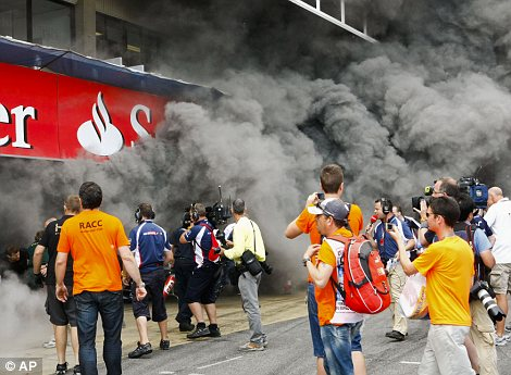People observe the smoke billowing out of the Williams team garage destroyed by the fire at the end of the Spanish Grand Prix at the Montmelo racetrack near Barcelona