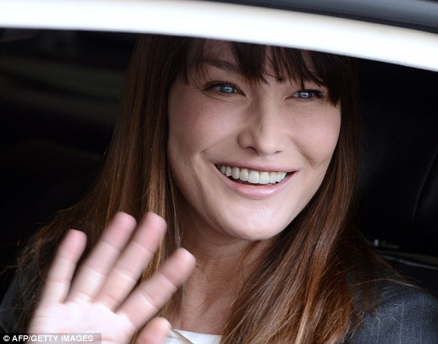 Carla waves as she leaves the Elysee Palace in a car with her husband