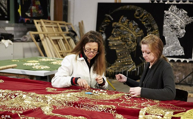 Ann, left, and her assistant at work on the banner which is being created to decorate the sumptuous royal barge that will carry the Queen and Duke of Edinburgh during the Thames Diamond Jubilee Pageant