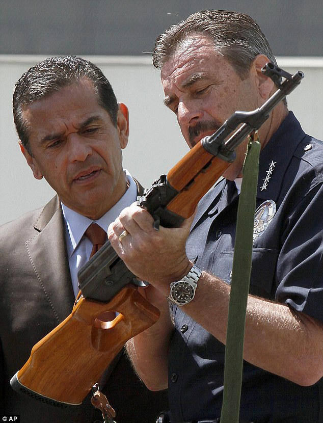 Police Chief Beck (right) and Los Angeles Mayor Villaraigosa (left) inspect an AK-47 assault rifle that was turned in during the weekend buyback program.