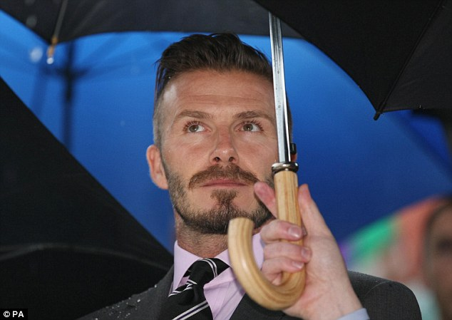 Ambassador: David Beckham shelters from the rain during a wet handover ceremony