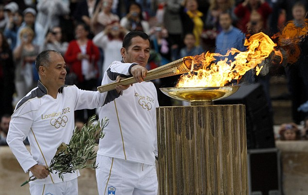 Lighting the flame: Greek veteran weighlifter Piros Dimas and Chinese gymnast Li Ning light a cauldron with the Olympic Flame inside the Panathenaic stadium in Athens