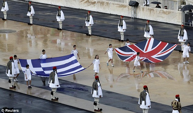 Flags: The British and Greek flags are carried into the Panathenaic stadium during an Olympic Flame handover