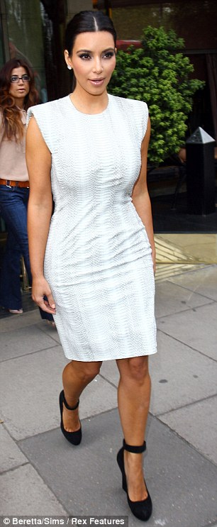 Curves on show: Kim has put on quite the fashion show since arriving in London, see right at Radio 1 today, and left leaving her central London hotel yesterday afternoon