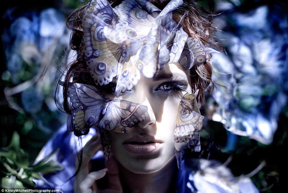 Danaus: A close-up of a model before a sunlit backdrop, peering through a veil of paper butterflies