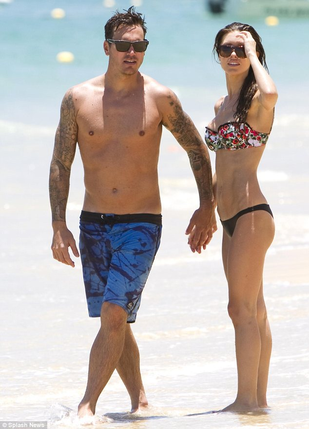 Loved up: The pair looked happy and relaxed as they held hands while dipping their toes in the water