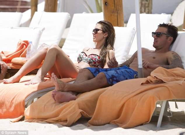 Lounging around: Audrina and Corey dried off by lying in the sun after their swim in the sea