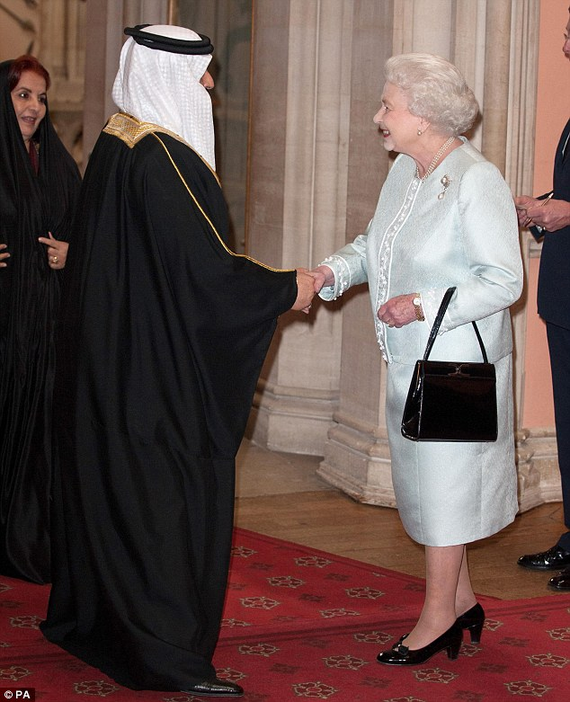 Controversial: Queen Elizabeth greets the King of Bahrain at today's lunch, while angry demonstrators outside the castle protested against the monarch's decision to invite the Middle Eastern leader