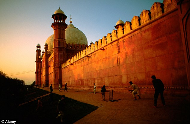 Delhi's Red Fort gives off a warm glow as locals enjoy a game of cricket